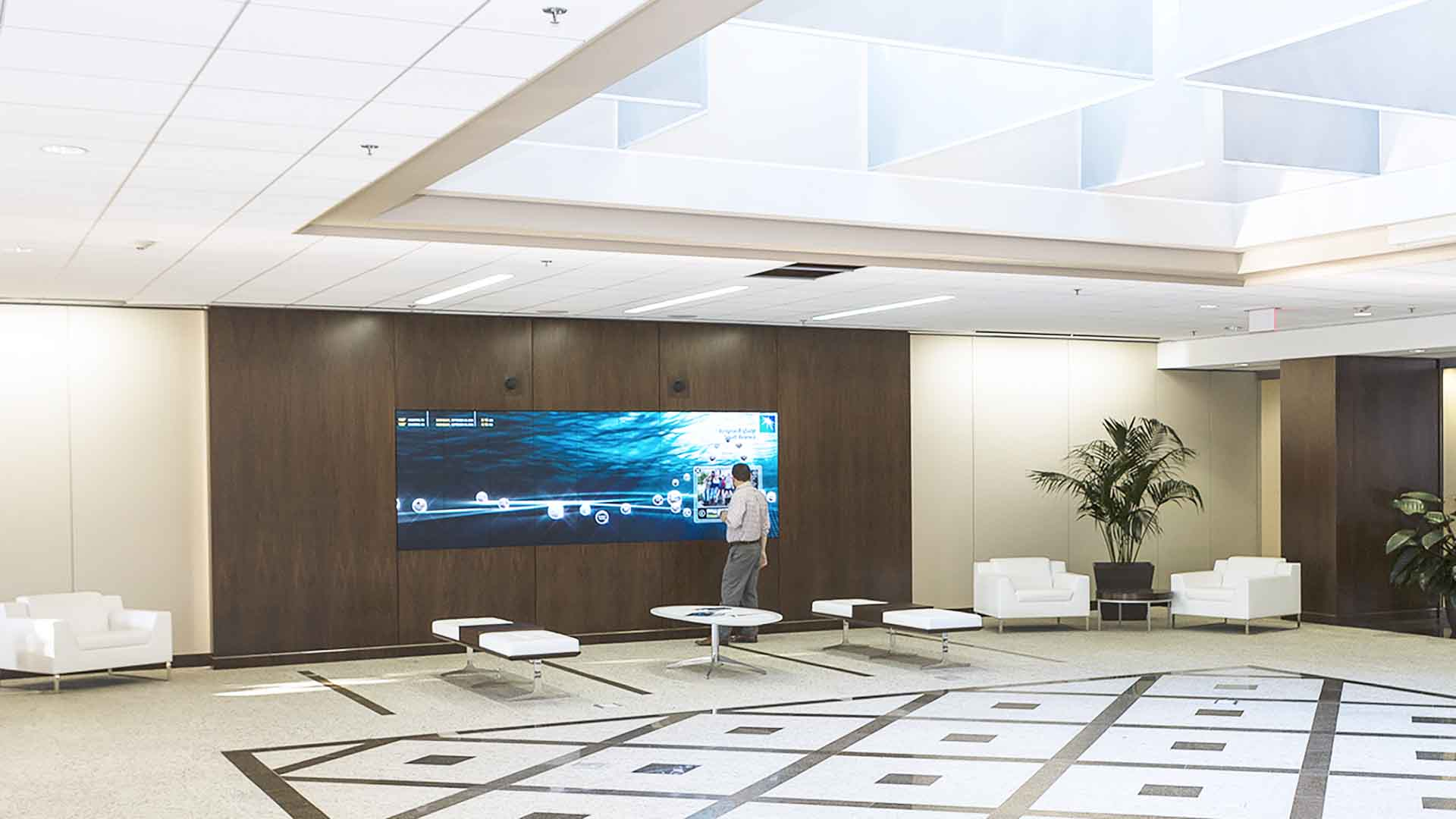Lobby area with big custom interactive media screen integrated in dark wood