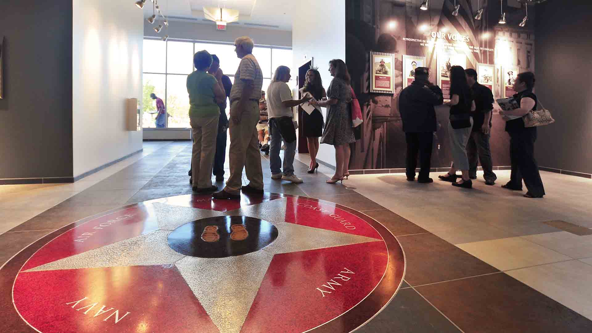 View of museum exhibit with custom graphic tile on floor and framed photographs of military men on wall.