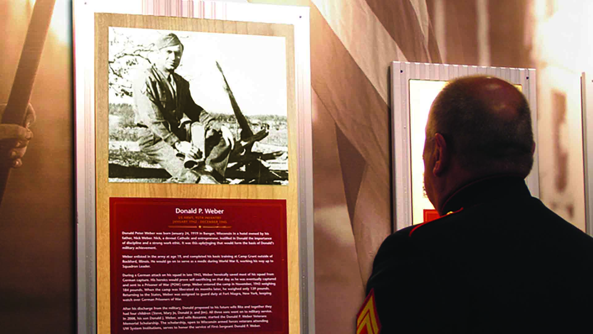 Man in military outfit looking at framed photographs of military men.