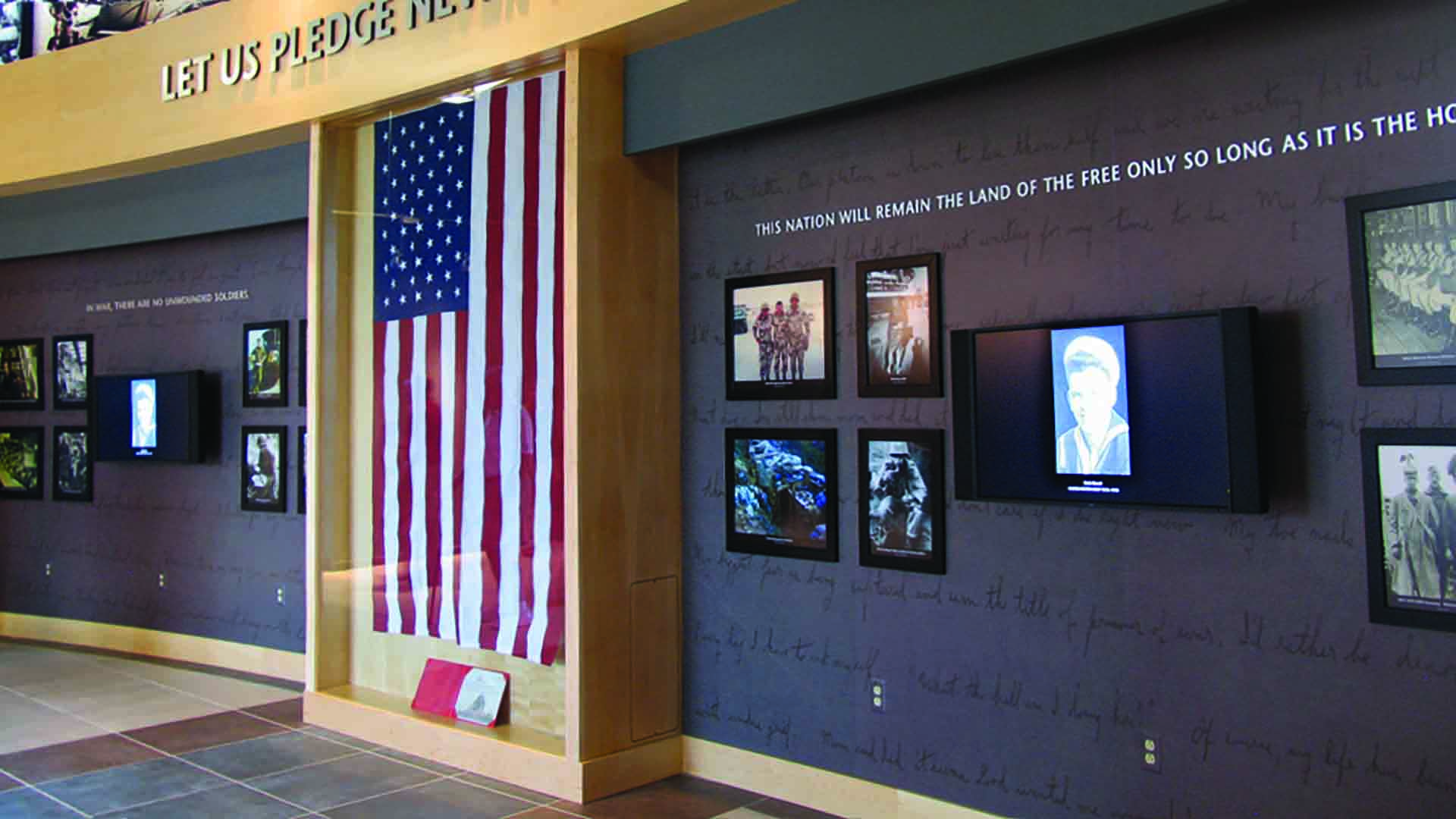 Flag hanging on wall next to media and photographs of men who have served