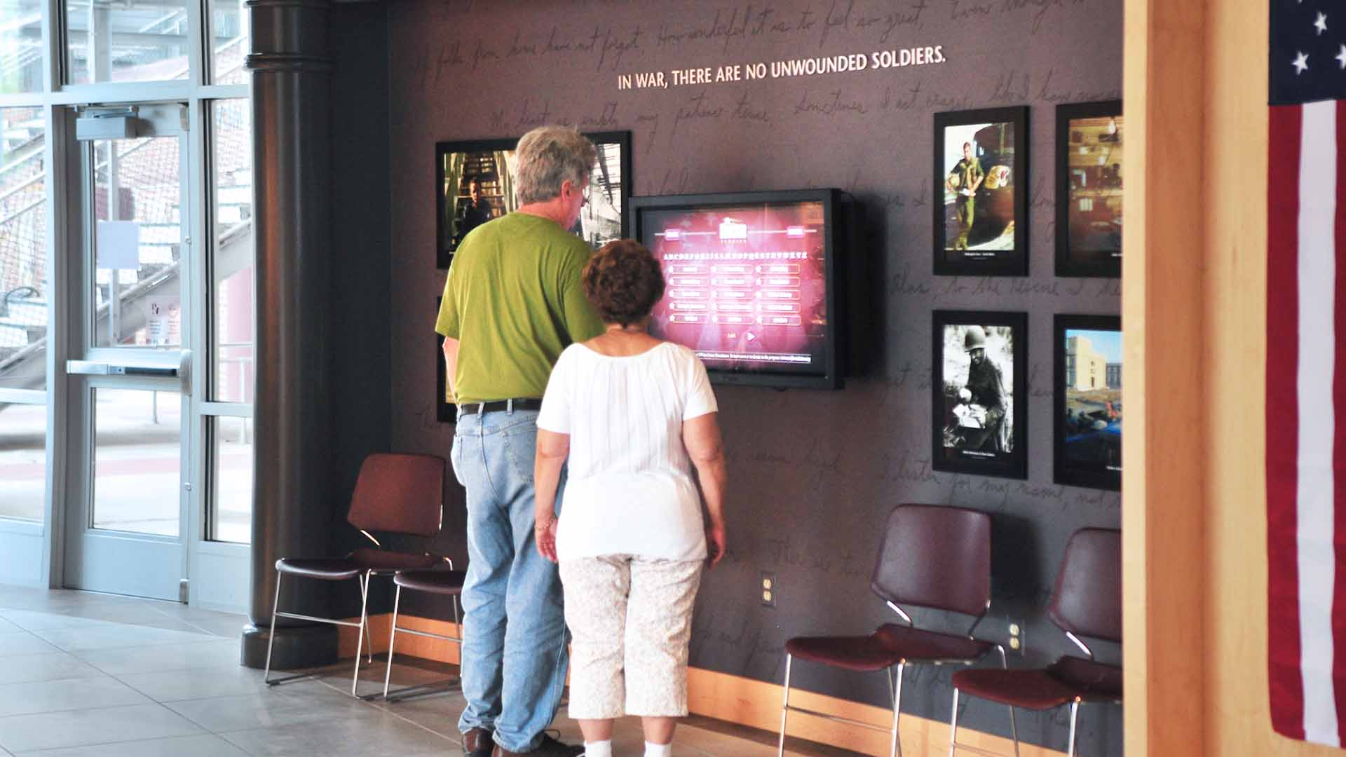 Couple viewing media exhibit about fallen soldiers