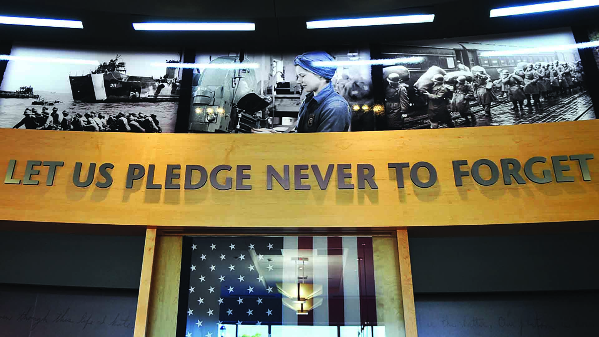 "Dimensional lettering reads ""Let us pledge never to forget"". Wall has flag in case and imagery of people who have helped in war times."
