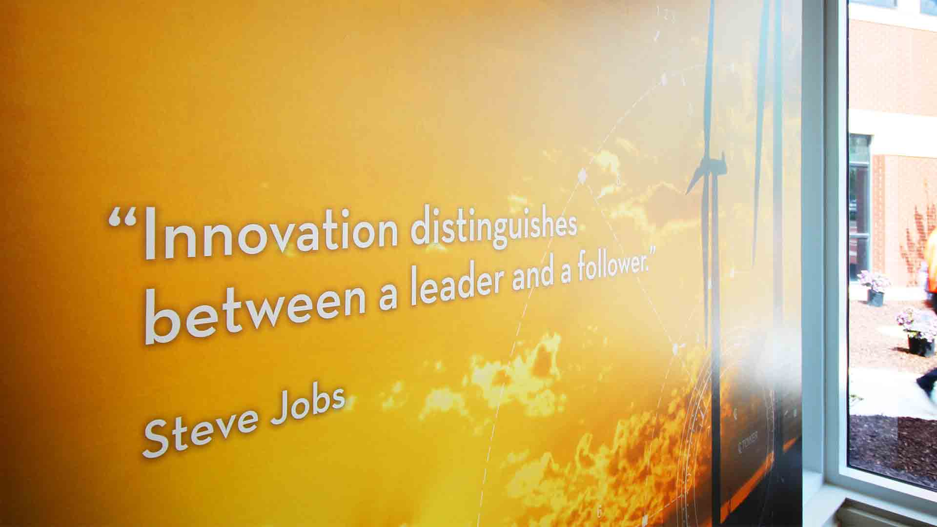 Close up view of wall mural graphic of wind turbines and quote