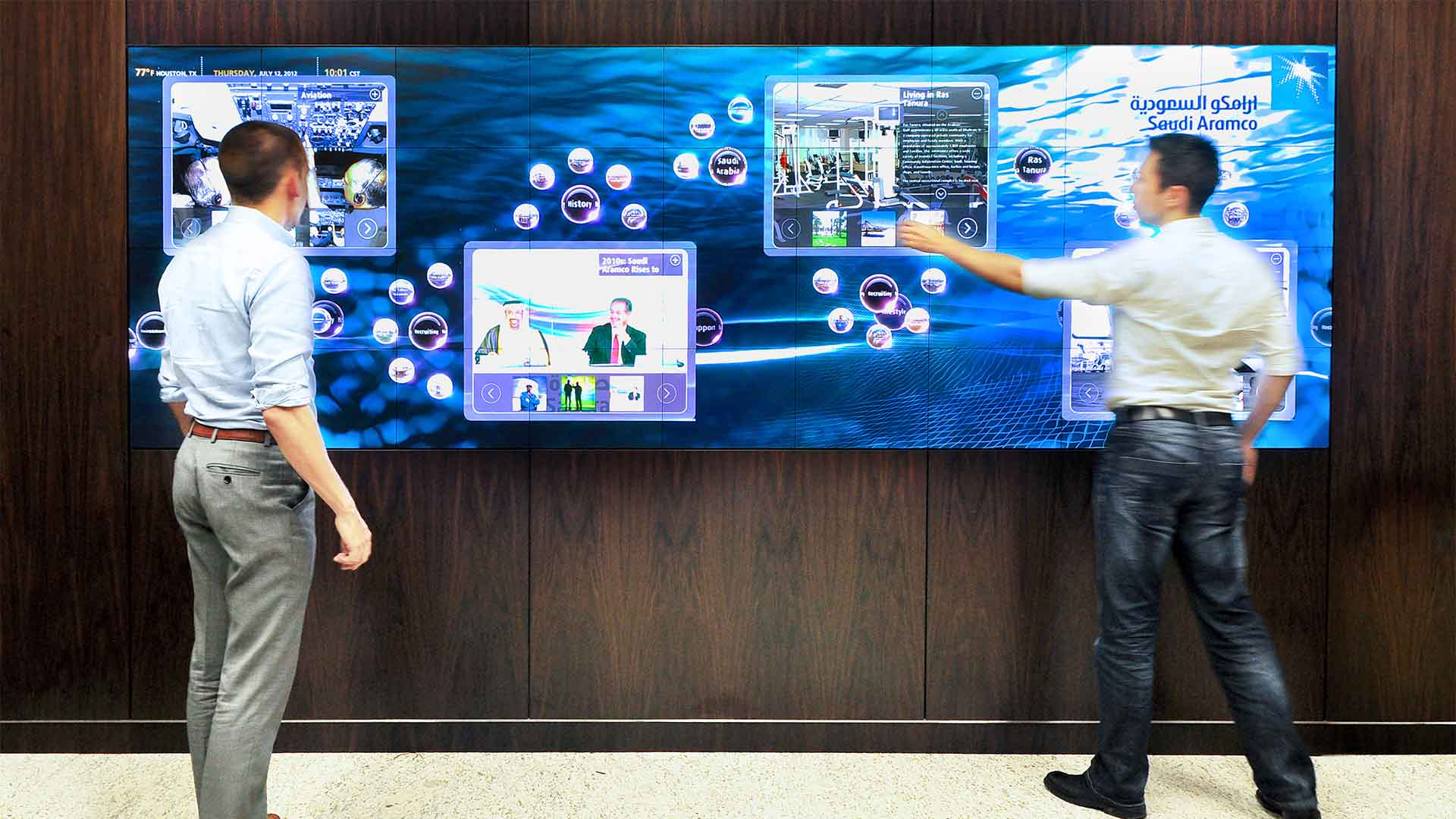 Two men using the interactive media exhibit to display information and utilize its content management system