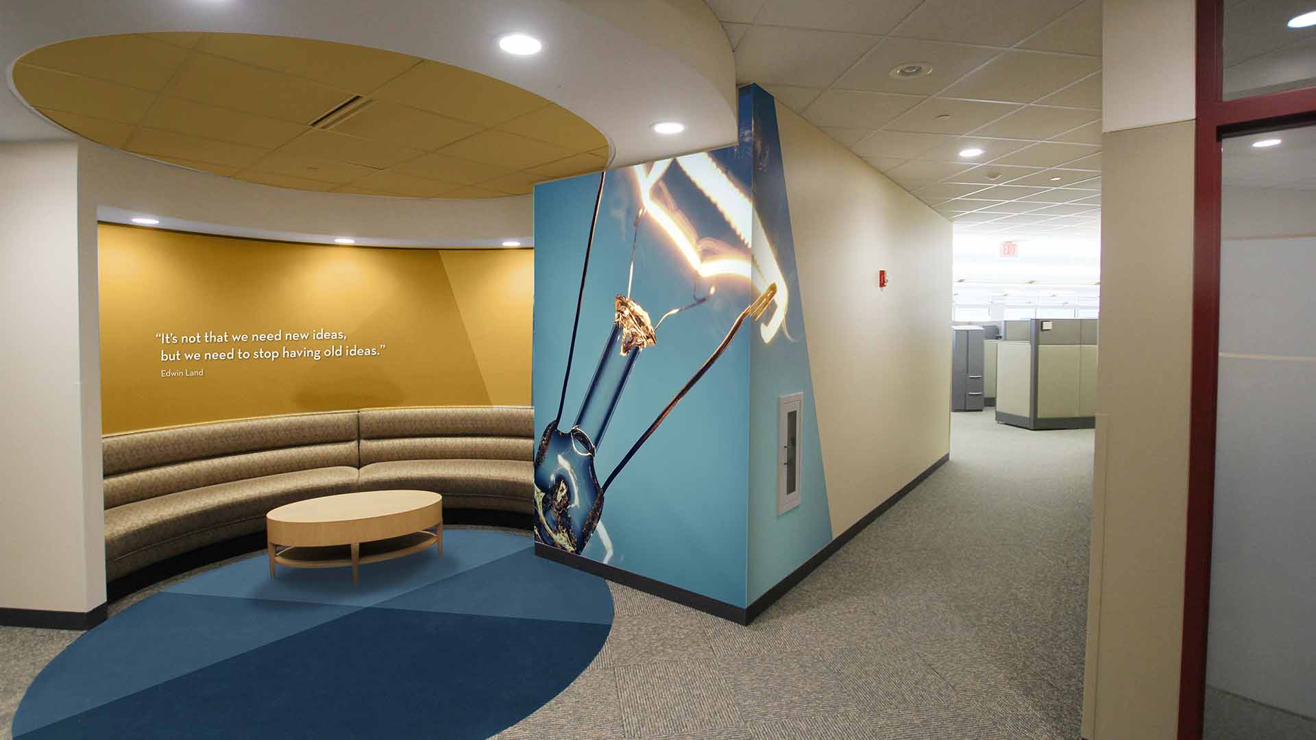 Area with seating has custom wall graphics and custom finishes relating to logo