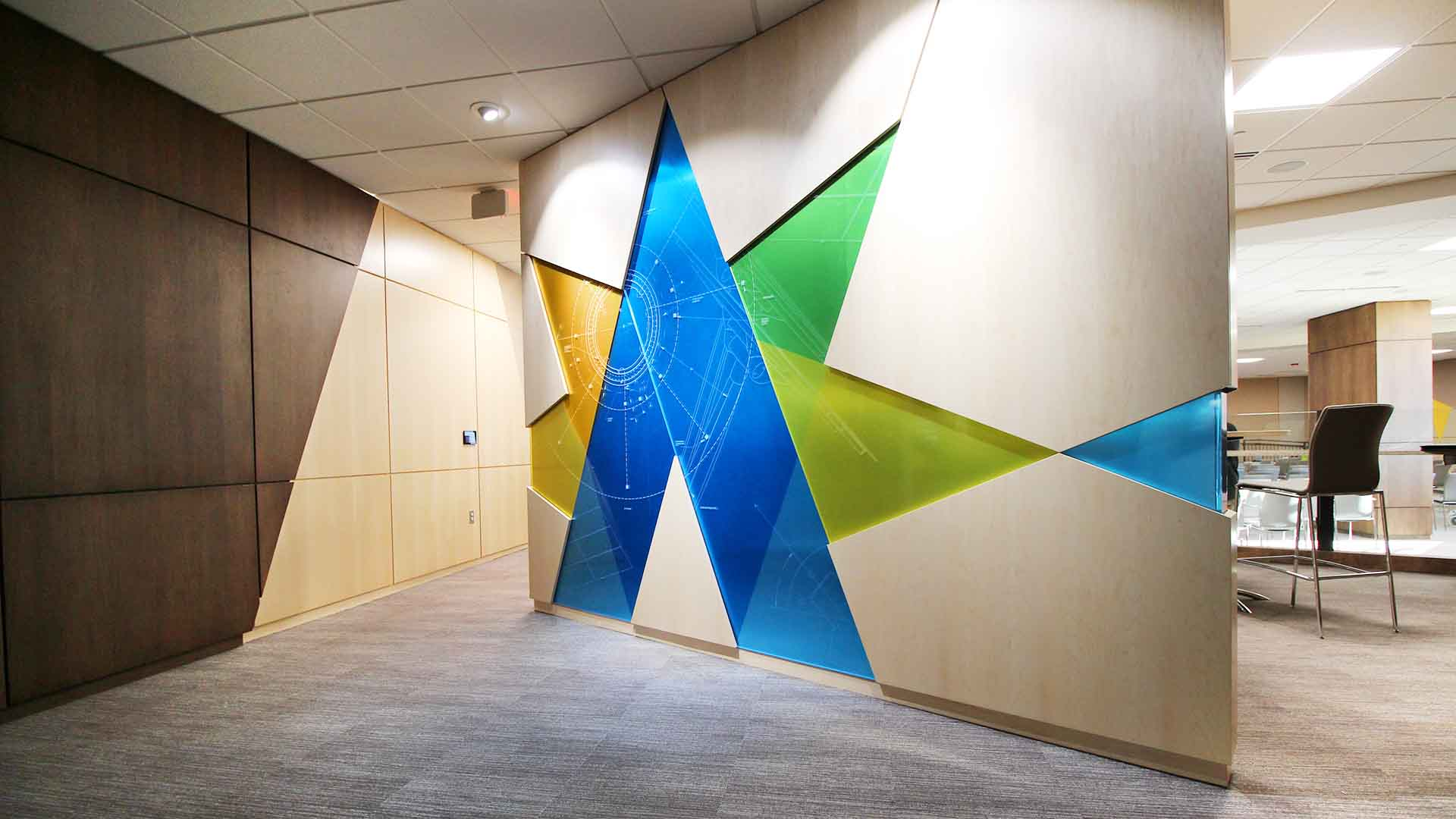 Inside conference center is a feature wall with the alliant energy logo in full color in a wood wall with an overlay of architectural drawings of energy structures