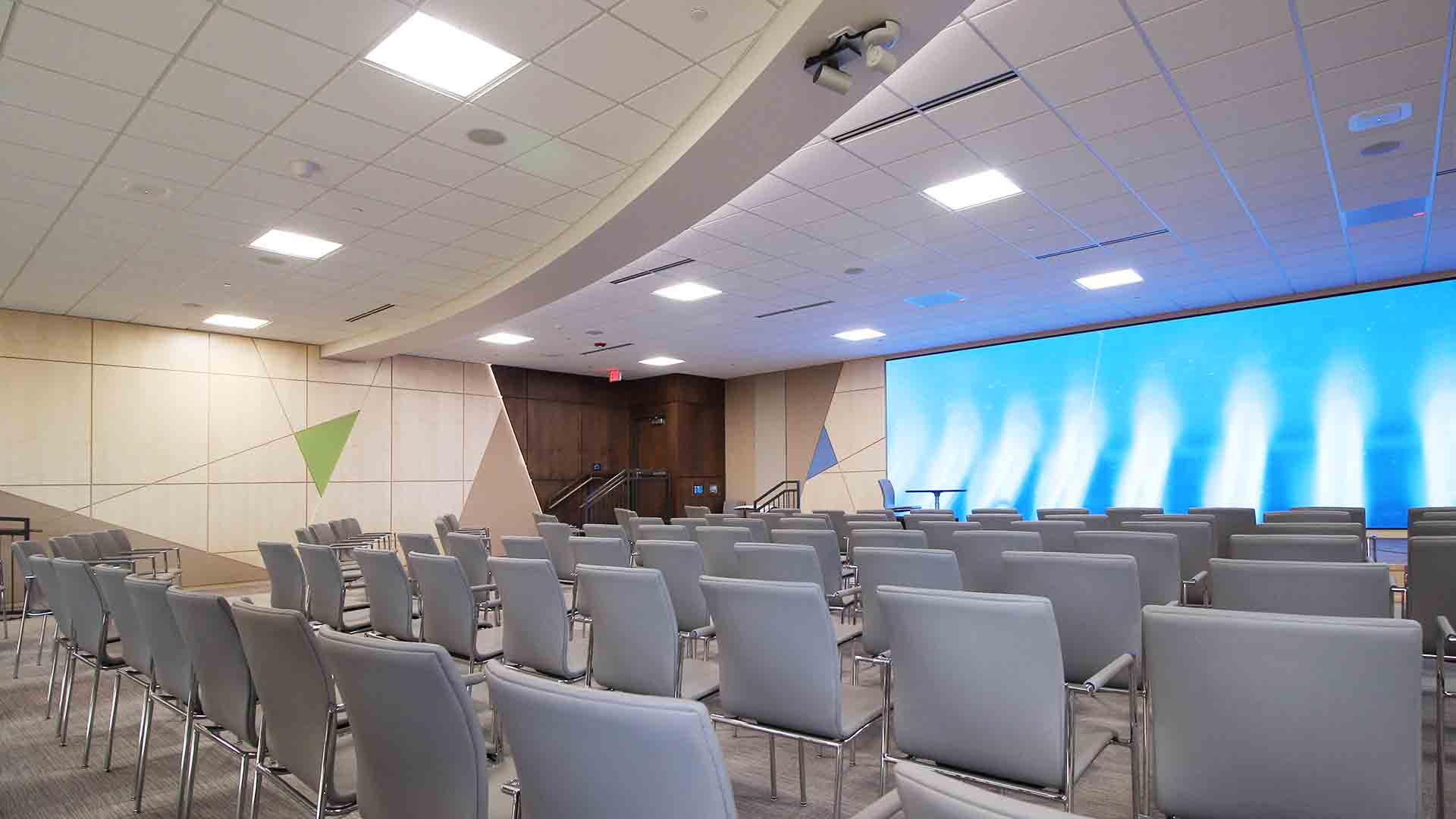 Conference center room screen with custom millwork showing varied stained woods and LED edge lighting as well as colored acoustic panels in patterns inspired by the Alliant Energy logo