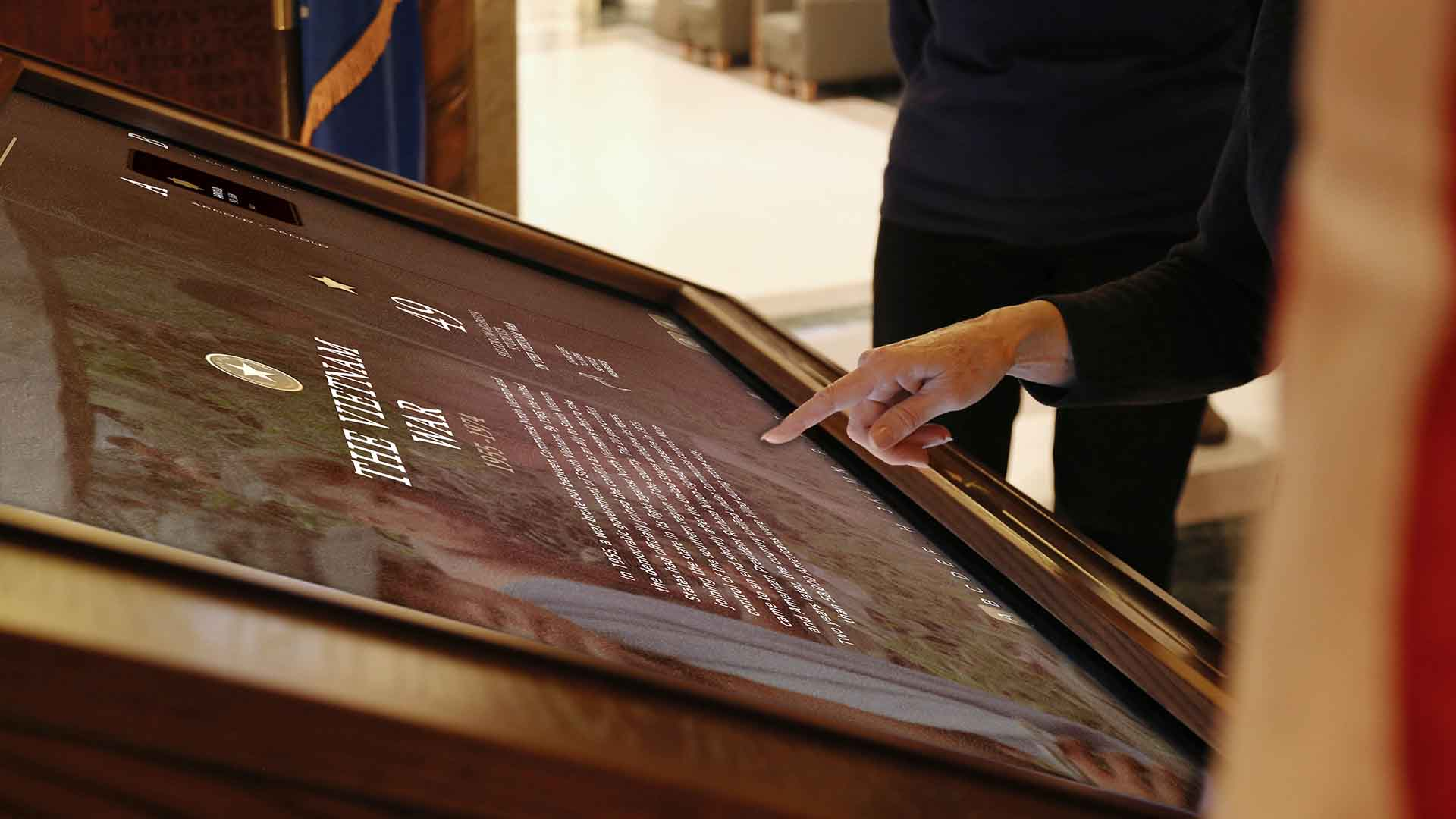 Close up view of woman interacting with UW Gold Star Honor Roll Kiosk