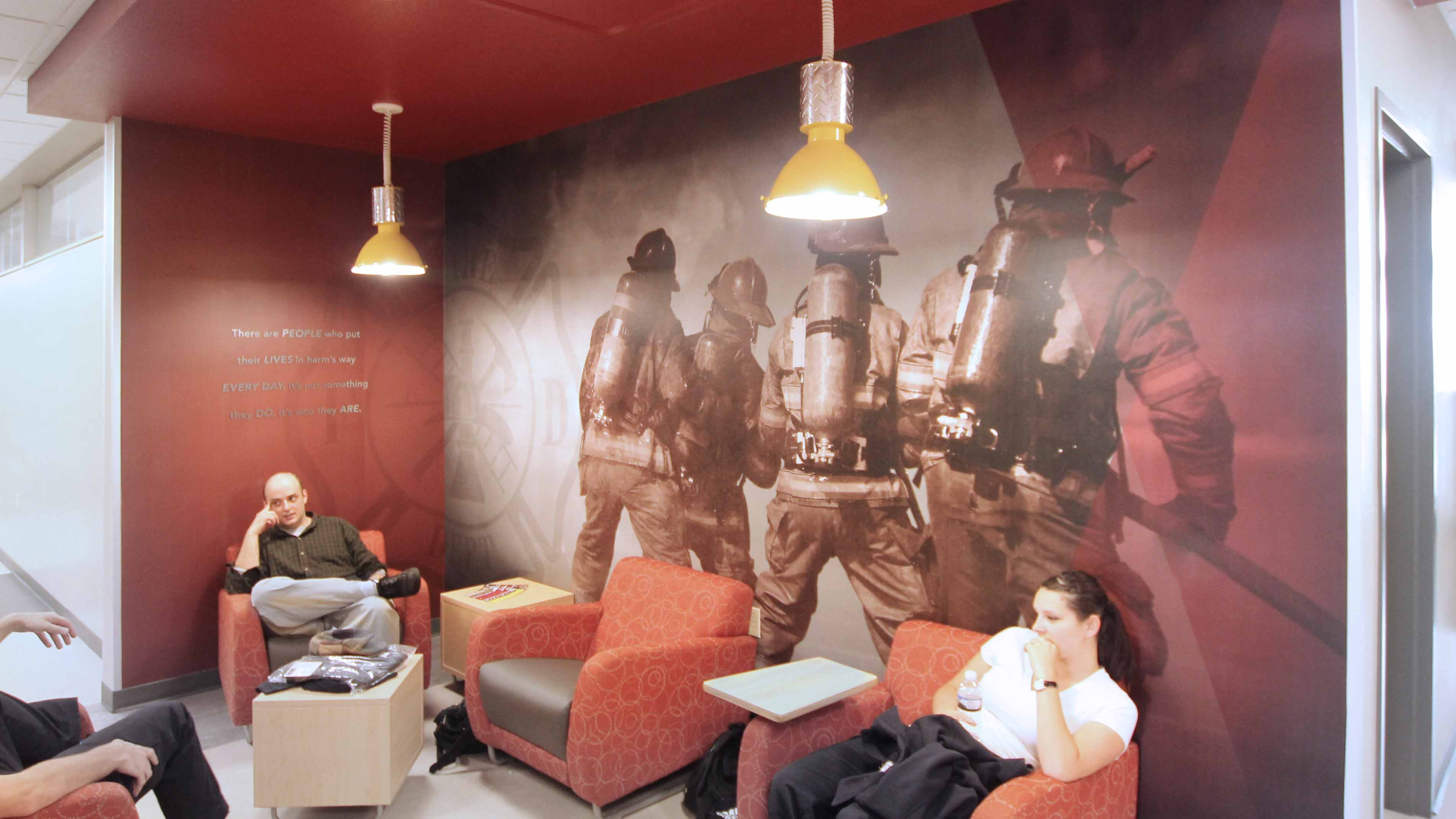 Fox Valley Technical College firefighter Mural in Hallway with students sitting against it